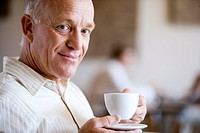 Senior man drinking cup of coffee in caf®, smiling, close-up, side view, portrait