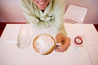 Man sitting at caf&#174; table, drinking cappuccino, smiling, front view, elevated view wide angle