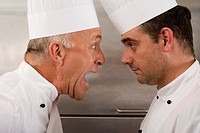 Angry senior chef yelling at junior chef in commercial kitchen, face to face, close-up, profile