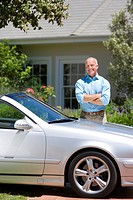 Proud senior man standing beside parked convertible car on driveway in front of house, arms folded, smiling, portrait