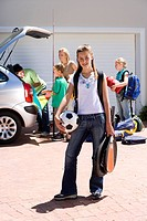 Family loading camping equipment into parked car boot on driveway, girl 11-13 carrying rucksack, soccer ball and tennis racquets in foreground, smilin...