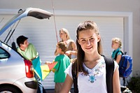 Family loading camping equipment into parked car boot on driveway, focus on girl 11-13 standing in foreground, smiling, portrait