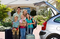 Family standing with luggage beside open boot of parked car on driveway, children 8-10 holding cuddly toys, smiling, portrait