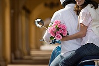 Couple riding on motor scooter near colonnade, woman holding bouquet of pink flowers, looking over shoulder, smiling, mid-section, rear view