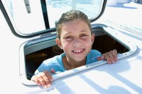 Girl 8-10 sticking head through open sailing boat cabin window, smiling, close-up, portrait