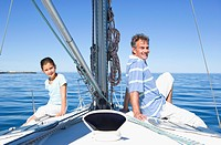 Father and daughter 8-10 sitting back to back at bow of sailing boat, smiling, side view, portrait