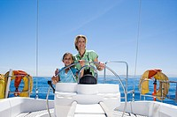 Mother and daughter 8-10 standing at helm of sailing boat out at sea, steering, smiling, front view, portrait