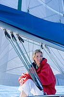 Woman in red jacket sitting on deck of sailing boat below sail, smiling, side view