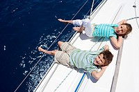 Boy and girl 8-10 lying on deck of sailing boat out to sea, feet dangling over side, hands behind head, smiling, side view, portrait, elevated view