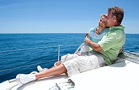 Couple sitting on deck of sailing boat out to sea, arms around each other, man holding rope, smiling, side view