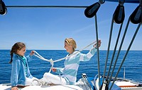 Mother and daughter 8-10 sitting at stern of sailing boat out at sea, tying knots in rope, smiling, profile