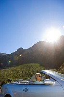 South Africa, Western Cape, senior woman driving silver convertible car along mountain road, smiling, side view lens flare