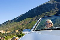 South Africa, Western Cape, senior woman driving silver convertible car along mountain road (thumbnail)