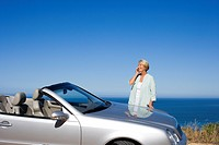 Senior woman standing beside parked convertible car on clifftop overlooking Atlantic Ocean, using mobile phone, smiling, side view