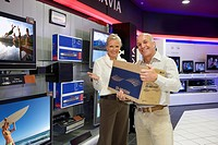 Mature couple shopping in television store, smiling, portrait
