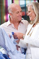 Mature couple smiling at each other in clothing store