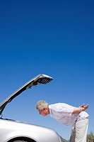 Senior man experiencing car trouble, looking at engine, bonnet raised against clear blue sky, profile