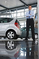 Car salesman standing near new cars in showroom, holding brochure, smiling, portrait surface level