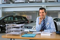 Car salesman sitting at desk in car showroom, smiling, portrait