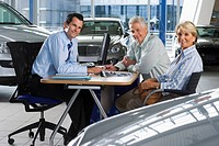 Car salesman and senior couple sitting at desk in large car showroom, smiling, side view, portrait