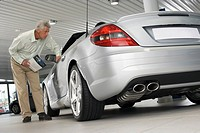 Senior man looking at new silver convertible car in large showroom, peering through window, holding brochure surface level, tilt