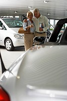 Senior couple looking at new silver convertible car in large showroom, man holding brochure, smiling