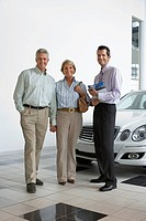 Car salesman and senior couple standing beside new car in showroom, salesman holding brochure, smiling, portrait