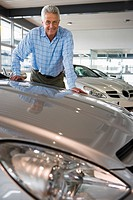 Senior man standing in large car showroom, leaning against bonnet of new silver car, smiling, portrait