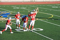 Opposing American football players competing for ball during competitive game, offensive receiver jumping up above rivals