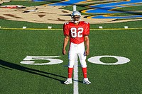 American football player, in red football strip and protective helmet, standing on pitch at 50 yard line, front view, portrait