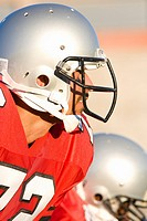 American football player wearing red football strip and protective helmet, close-up, profile, focus on foreground