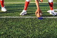 American football running back, in red football strip, crouching with ball in scrimmage line during competitive game, front view, low-section