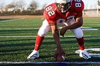 American football running back, in red football strip, crouching with ball in scrimmage line during competitive game, front view