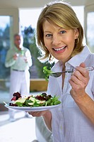 Mature woman eating salad on plate at home, senior man in background, focus on woman, smiling, side view, portrait
