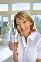Mature woman drinking glass of water at home, senior man in background, focus on woman, smiling, portrait