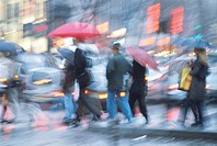 People crossing street with umbrellas blurred motion