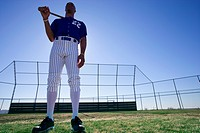 Baseball batter, wearing number ÔÇÿ22ÔÇÖ blue uniform, standing on pitch with bat resting on shoulder, front view, portrait, surface level, backlit