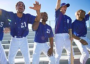 Excited baseball team jumping up from bench in stand during competitive baseball game, cheering, front view backlit