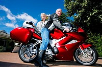 Senior couple posing beside red motorbike on driveway, man sitting on motorbike, smiling, side view, portrait surface level
