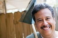 Smiling man holding rake