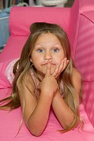 Young girl with big blue eyes stares into the camera with finger at lips