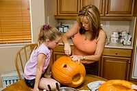 Mother helps daughter carve a halloween pumpkin