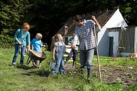 Parents with three children 5-9 gardening outside cottage (thumbnail)