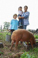 Father and children 5-6 7-9 with pig in sty portrait (thumbnail)