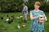 Couple feeding hens in garden portrait (thumbnail)