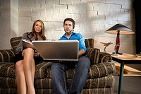 Woman and man on sofa with laptop