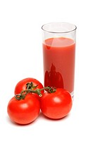 Glass of tomato juice with tomatoes on white background
