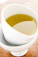Olive oil in white pouring bowls on olive tree wooden chopping board