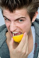 Man biting lemon