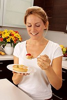 Woman In Kitchen Eating Fruit Pastry / Tart